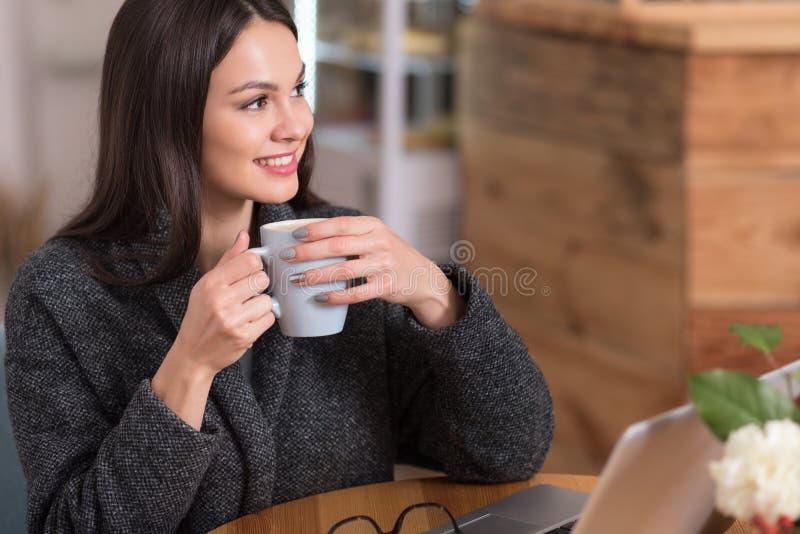 Mujer encantadora feliz que goza de su café imágenes de archivo libres de regalías
