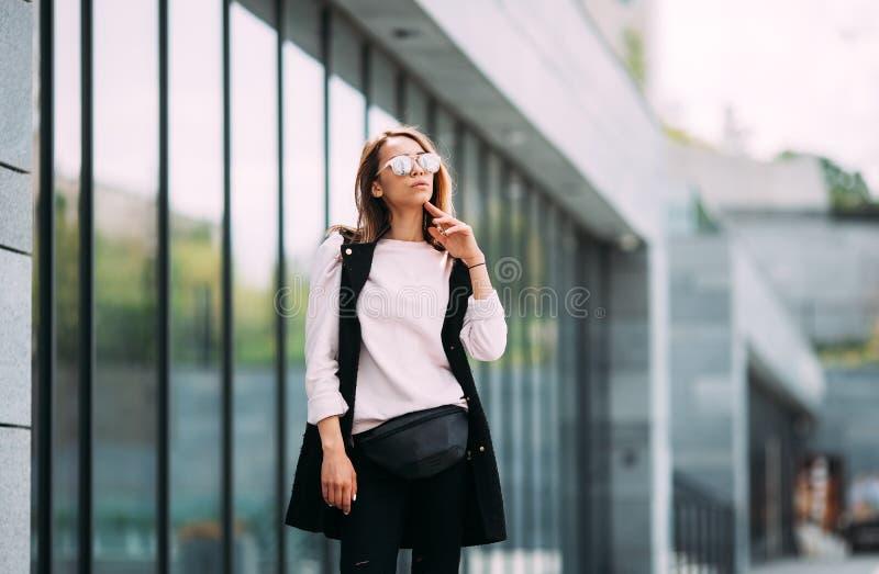 Mujer encantadora joven en las gafas de sol de moda que miran lejos foto de archivo