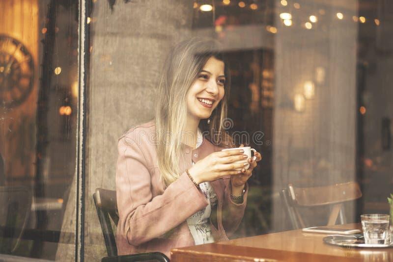 Mujer encantadora joven pasar tiempo mientras que se sienta en la cafetería durante tiempo libre, hembra atractiva con la sonrisa fotos de archivo libres de regalías