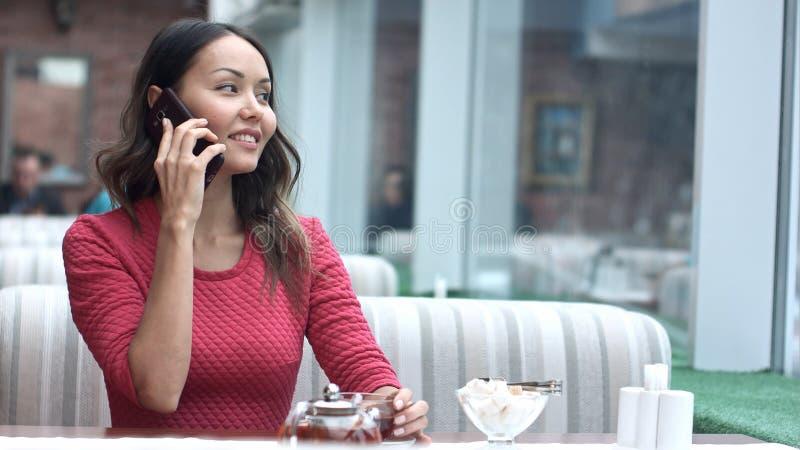 Mujer encantadora joven que llama con el teléfono de célula mientras que se sienta solamente en café imágenes de archivo libres de regalías