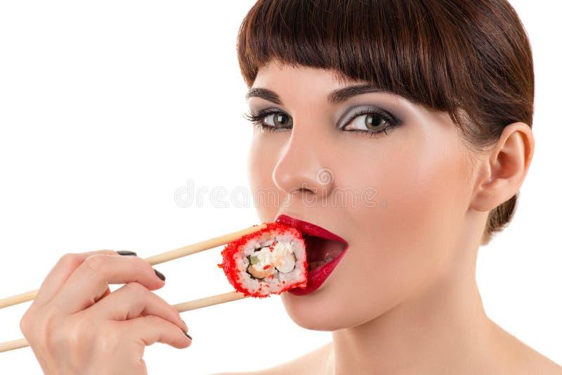Mujer encantadora que come el rollo con el caviar rojo imagenes de archivo