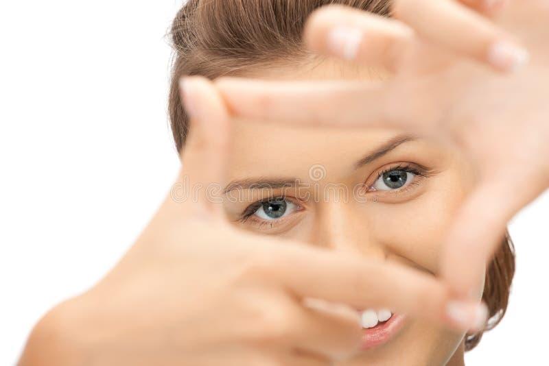 Mujer encantadora que crea un marco con los dedos imagen de archivo