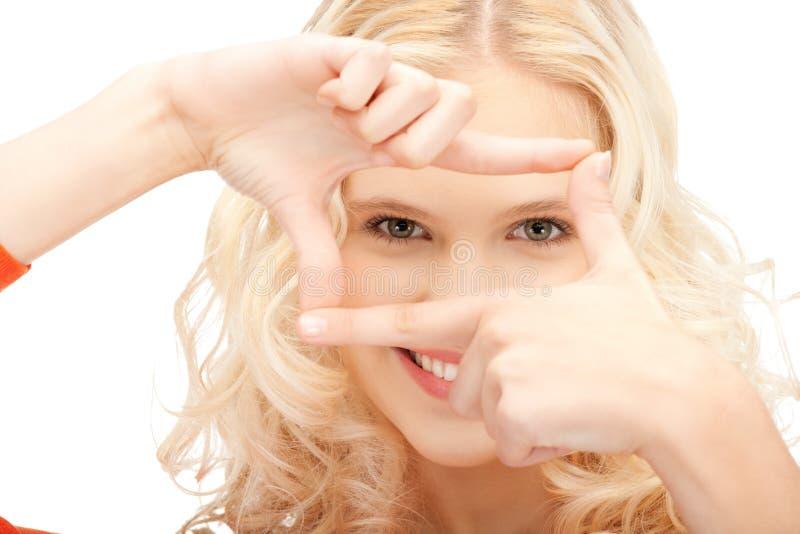 Mujer encantadora que crea un marco con los dedos fotografía de archivo
