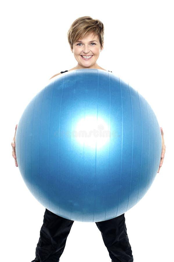 Mujer encantadora que sostiene la bola azul grande de la aptitud imagen de archivo libre de regalías