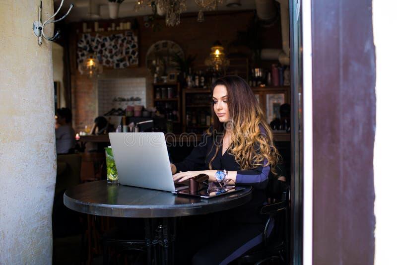 Mujer encantadora que trabaja en el dispositivo del cuaderno durante tiempo libre en cafetería imagen de archivo libre de regalías