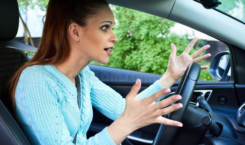 Mujer enfadada que conduce un coche imagenes de archivo