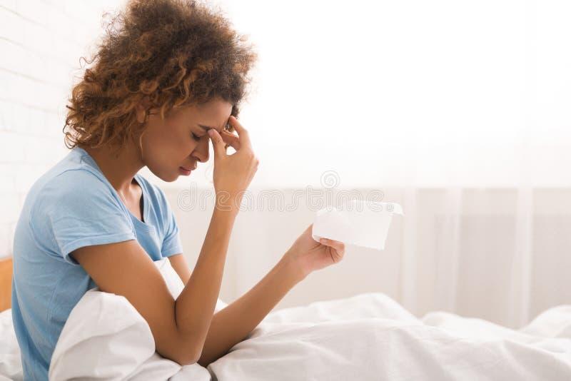 Mujer enferma afroamericana con los mocos, sentándose en cama foto de archivo libre de regalías