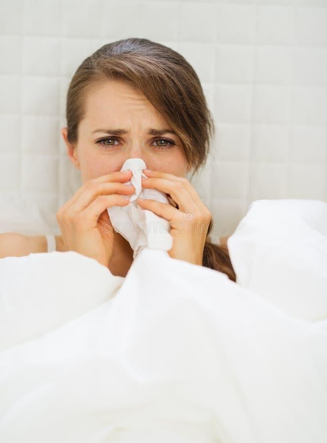 Mujer enferma con el pañuelo que pone en cama imagen de archivo libre de regalías