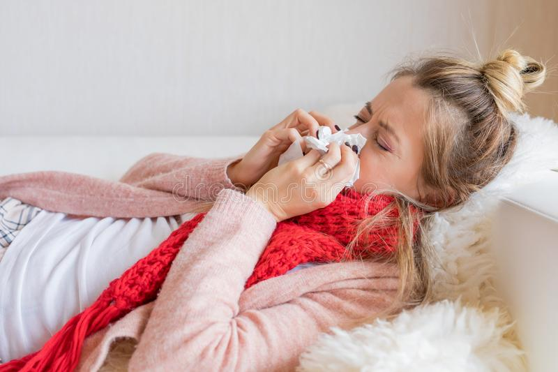 Mujer enferma con el tejido y la nariz corriente fotos de archivo