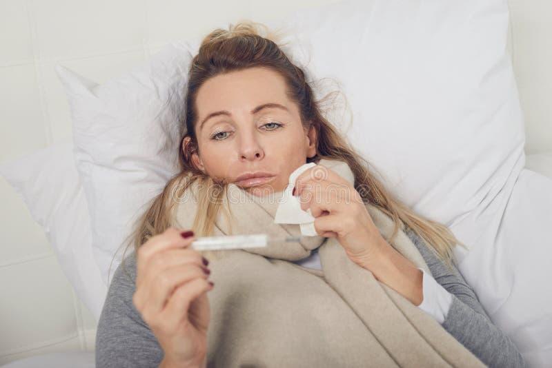Mujer enferma con una expresión desgraciada que toma su temperatura imagenes de archivo