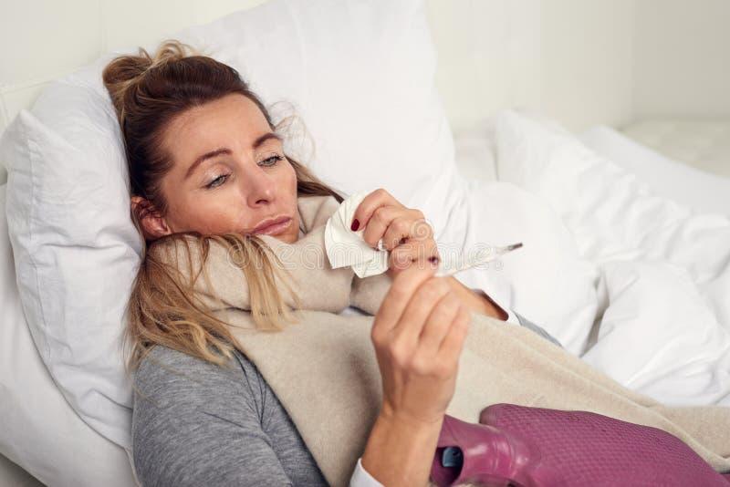 Mujer enferma con una expresión desgraciada que toma su temperatura imagen de archivo libre de regalías