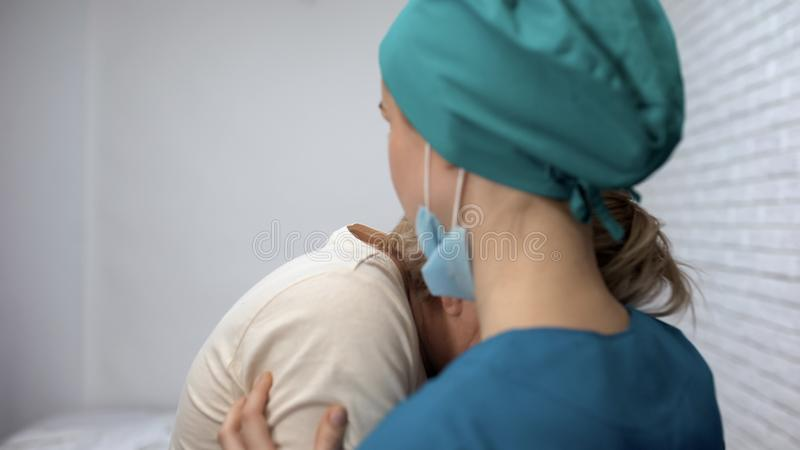 Mujer enferma desesperada que llora, doctor que intenta apoyar enfermedad paciente, incurable imagen de archivo