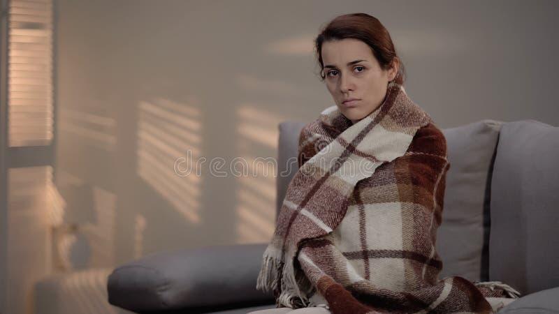 Mujer enferma desgraciada cubierta en la tela escocesa que mira la cámara, enfermedad terminal, clínica imagenes de archivo