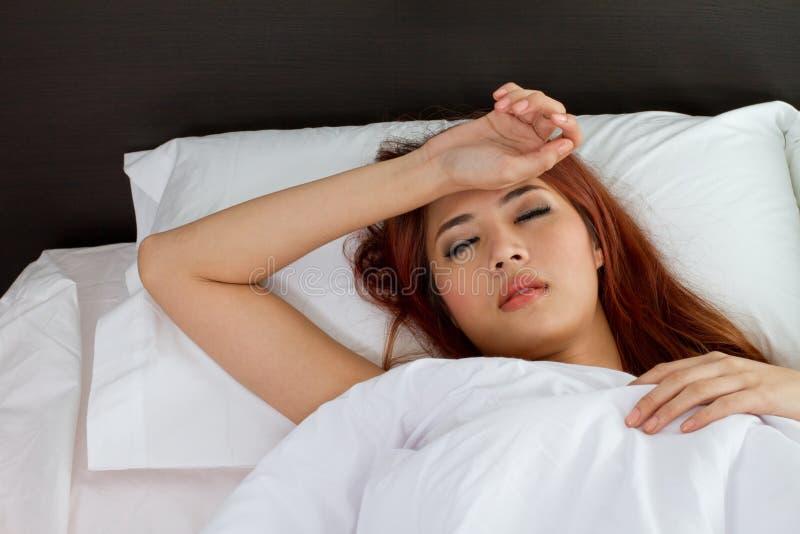 Mujer enferma en cama imagenes de archivo
