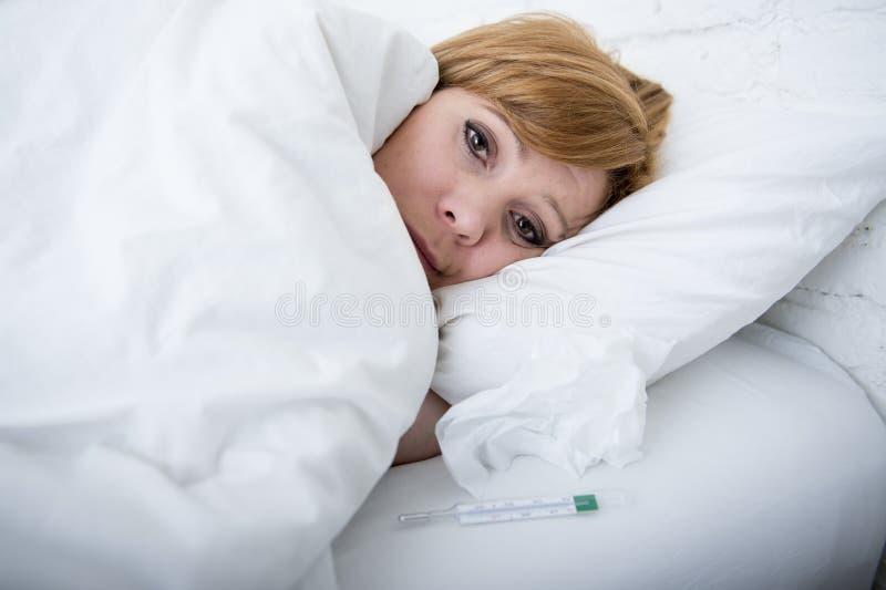 mujer enferma en cama con el virus frío de la gripe del invierno del sufrimiento débil febril del termómetro fotografía de archivo libre de regalías
