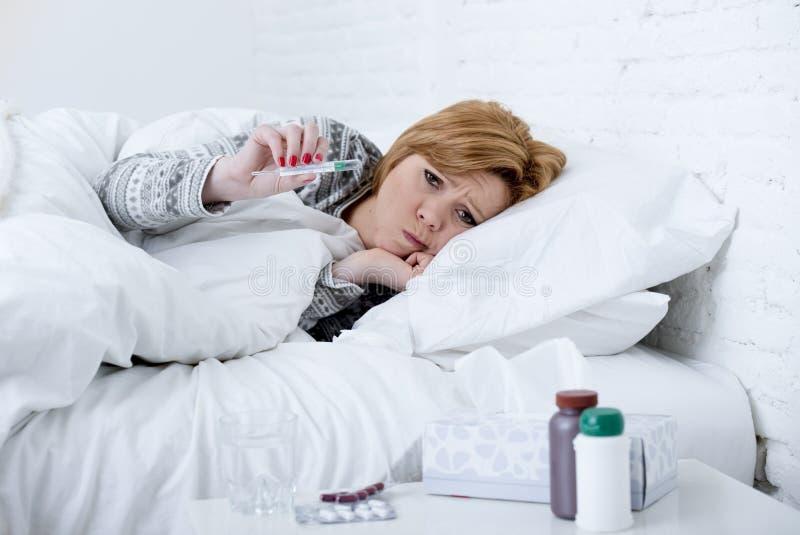 Mujer enferma en cama que comprueba temperatura con el termómetro que siente febril teniendo virus frío de la gripe del invierno imagenes de archivo