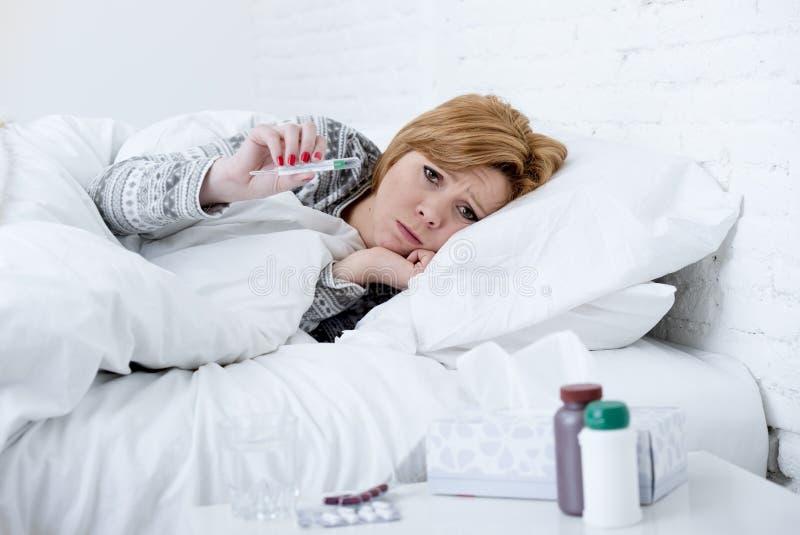 mujer enferma en cama que comprueba temperatura con el virus frío de la gripe del invierno del sufrimiento débil febril del termó imágenes de archivo libres de regalías