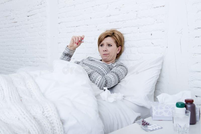 mujer enferma en cama que comprueba temperatura con el virus frío de la gripe del invierno del sufrimiento débil febril del termó fotos de archivo