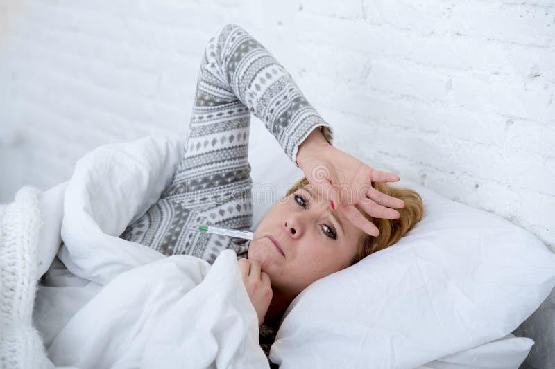 mujer enferma en cama que comprueba temperatura con el virus frío de la gripe del invierno del sufrimiento débil febril del termó fotografía de archivo