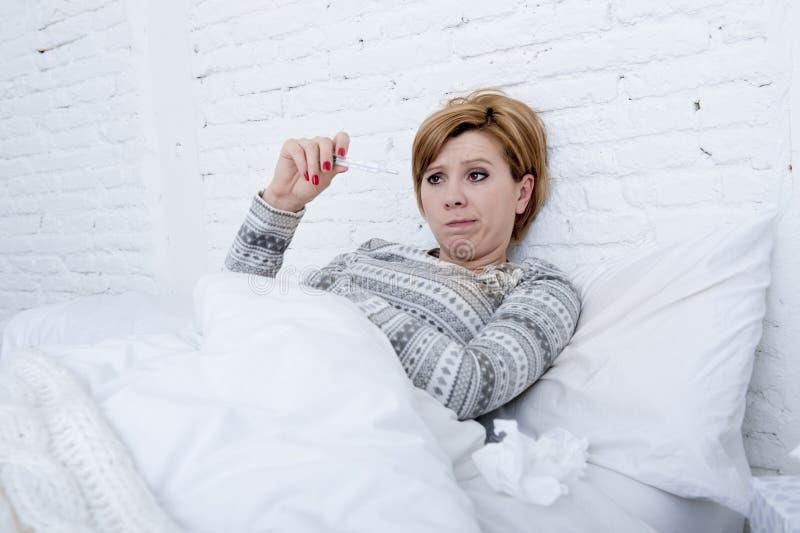 mujer enferma en cama que comprueba temperatura con el virus frío de la gripe del invierno del sufrimiento débil febril del termó fotos de archivo libres de regalías