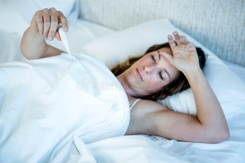 mujer enferma en cama que lee un termómetro imágenes de archivo libres de regalías