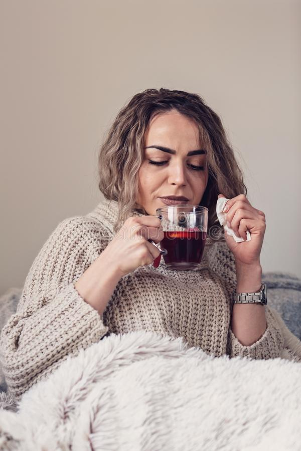 Mujer enferma gripe Frío cogido mujer El sentarse en el sofá Headach imagenes de archivo
