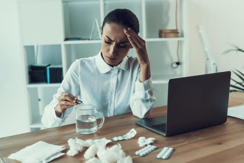 Mujer enferma joven en la camisa blanca que se sienta en oficina fotografía de archivo