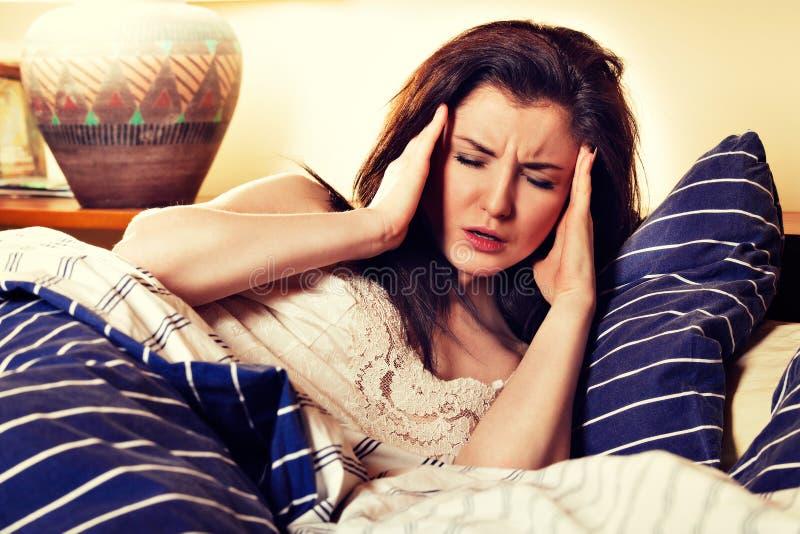 Mujer enferma joven que miente en su cama en dormitorio fotos de archivo libres de regalías