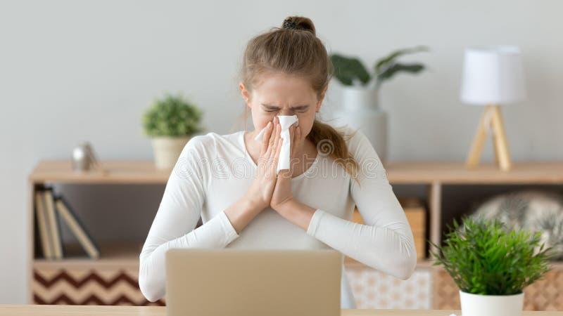 Mujer enferma joven que se sienta en el lugar de trabajo, nariz que sopla, sosteniendo el pañuelo foto de archivo