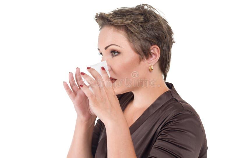 Mujer enferma joven que sopla su nariz imagen de archivo libre de regalías