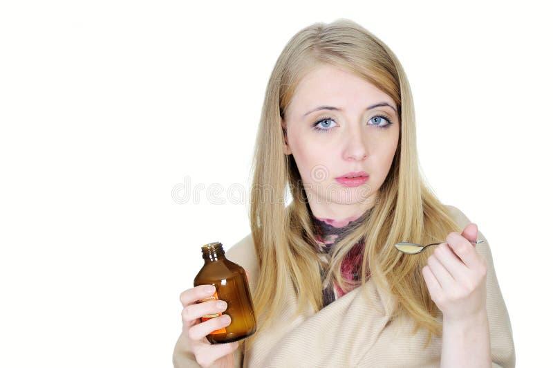 Mujer enferma joven que toma el jarabe imagen de archivo