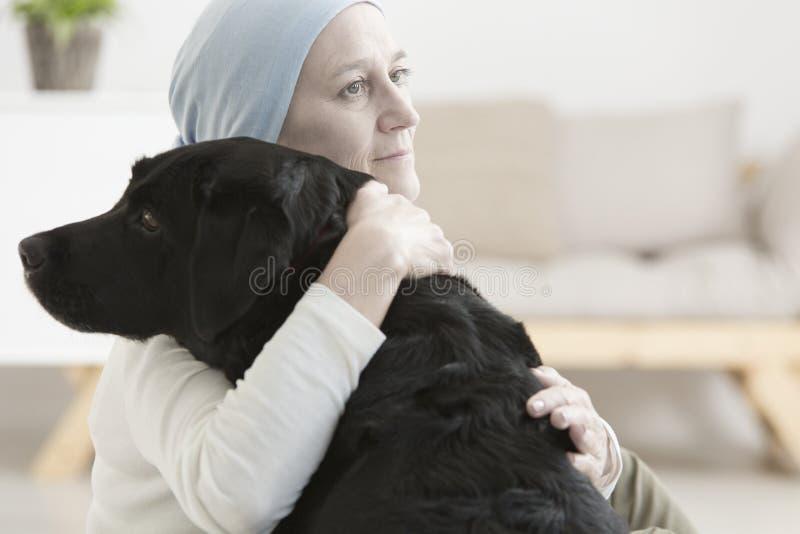 Mujer enferma que abraza el perro imagenes de archivo