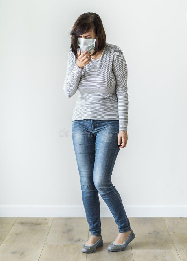 Mujer enferma que lleva la máscara quirúrgica imagenes de archivo