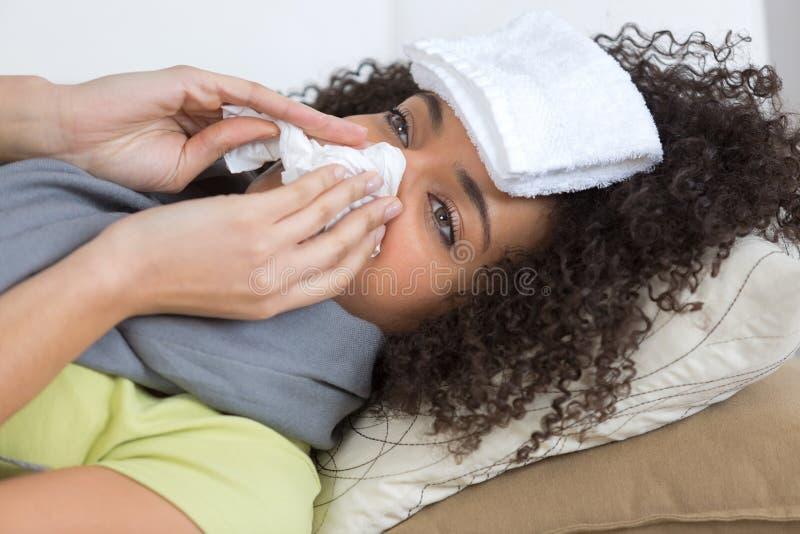 Mujer enferma que pone en la cama que estornuda fotos de archivo libres de regalías