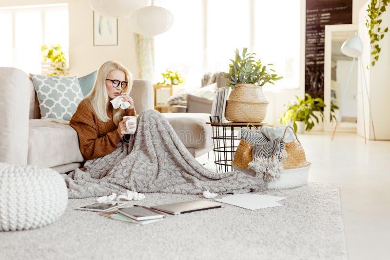 Mujer enferma que se sienta en el piso cubierto con una manta y una n que sopla fotos de archivo libres de regalías