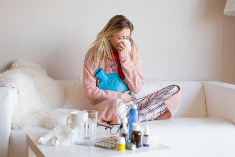 Mujer enferma que se sienta en sofá imagenes de archivo