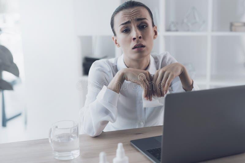 Mujer enferma que se sienta en su lugar de trabajo en la oficina Ella sienta y sostiene una servilleta de papel en sus manos foto de archivo
