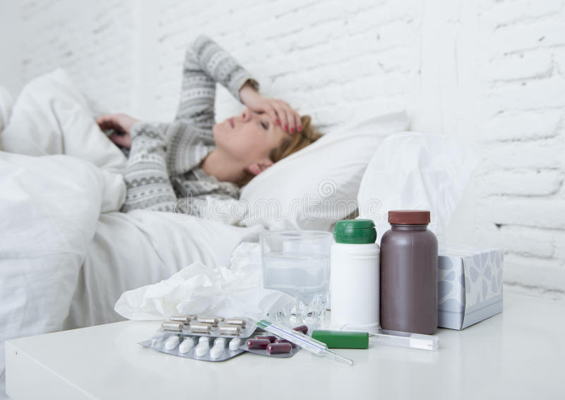 Mujer enferma que se siente mal la mentira enferma en el virus sufridor del frío y de la gripe del invierno del dolor de cabeza d imágenes de archivo libres de regalías