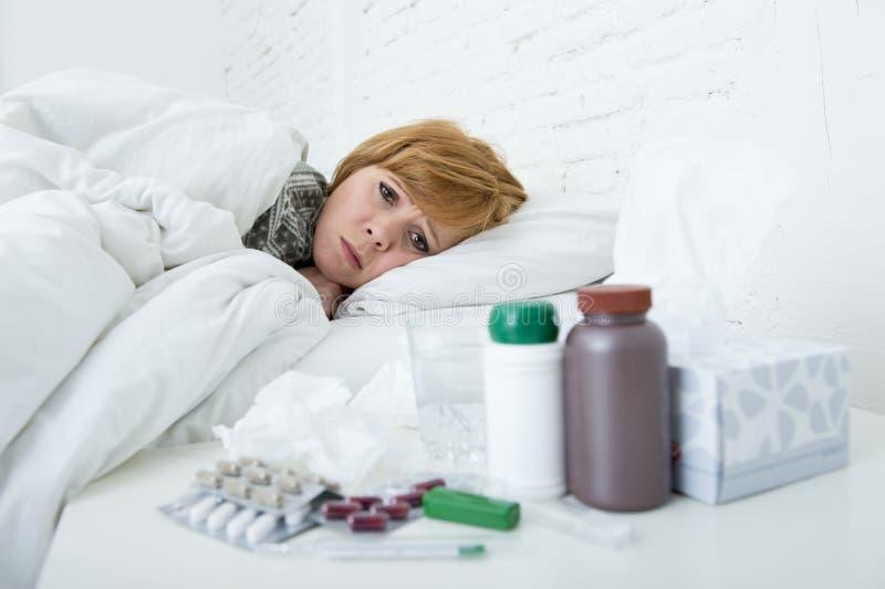 Mujer enferma que se siente mal la mentira enferma en el virus sufridor del frío y de la gripe del invierno del dolor de cabeza d fotografía de archivo