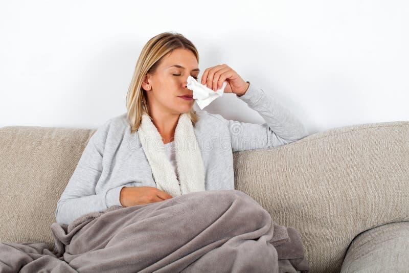 Mujer enferma que sopla su nariz foto de archivo