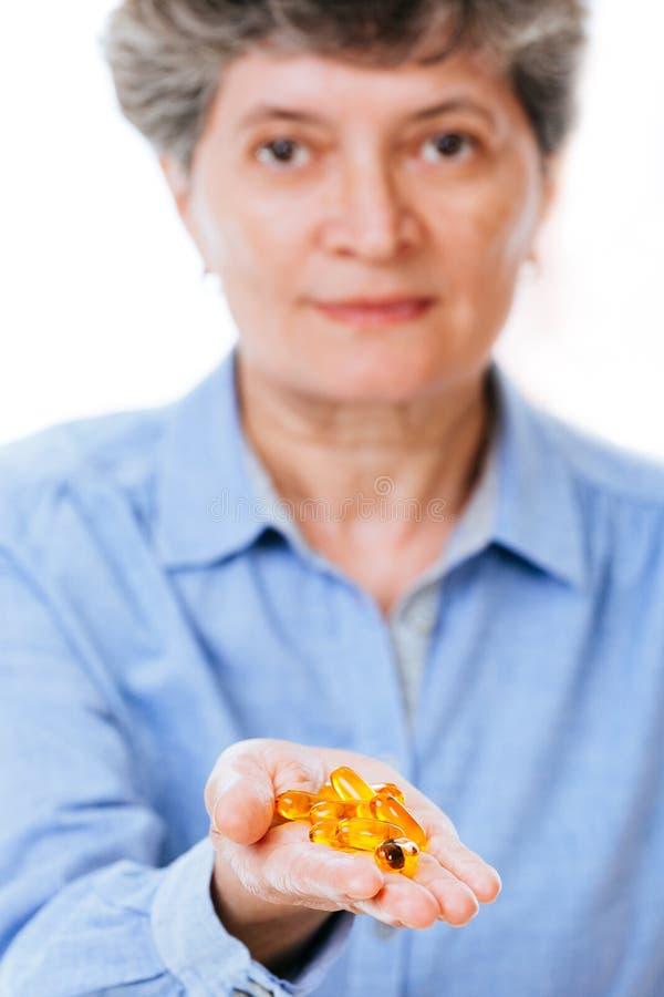 Mujer enferma que sostiene la medicación en sus manos fotografía de archivo libre de regalías