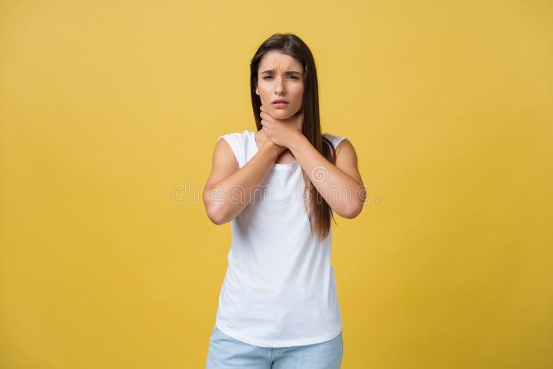 Mujer enferma que sufre de la garganta dolorida aislada sobre fondo amarillo fotografía de archivo