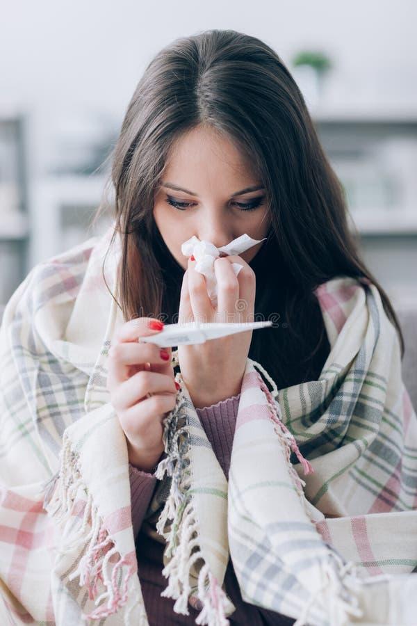 Mujer enferma que toma temperatura imagen de archivo