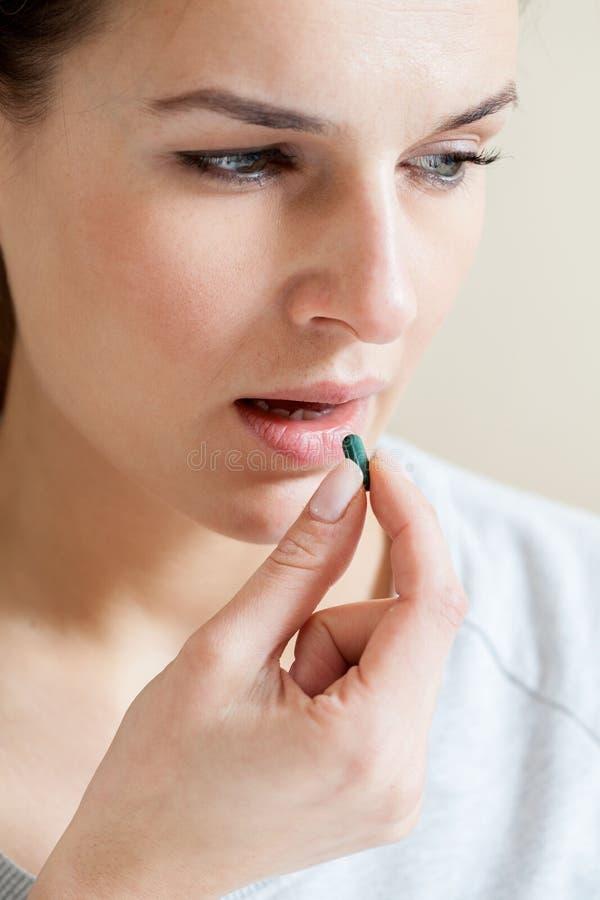 Mujer enferma que toma una píldora fotos de archivo