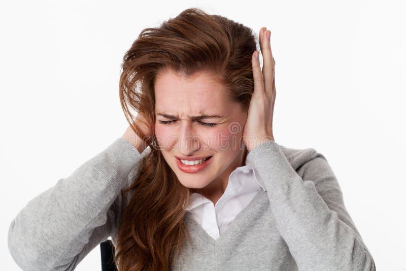 Mujer enferma 20s en el zumbido o el escuchar la música ruidosa fotografía de archivo libre de regalías