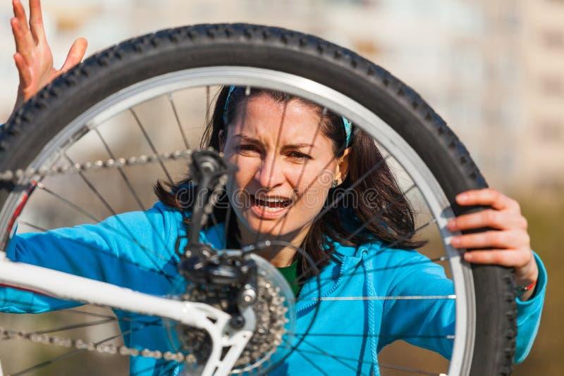 Mujer enojada con la bici dañada fotos de archivo