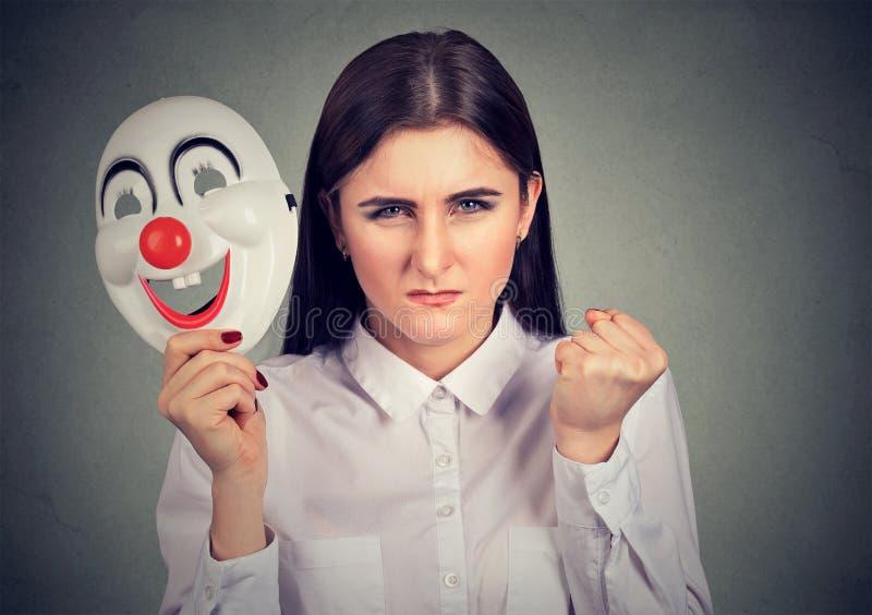Mujer enojada con la máscara del payaso foto de archivo