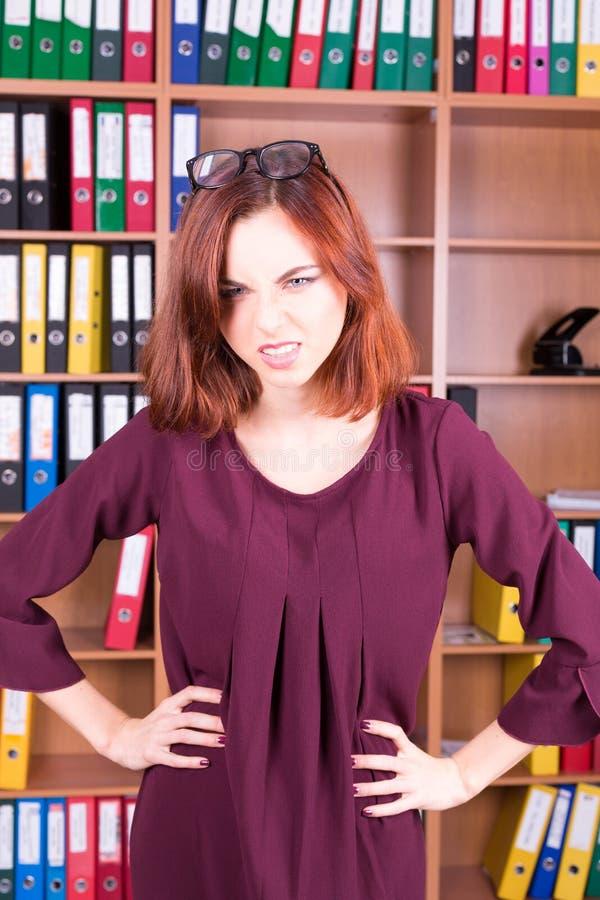 Mujer enojada en la oficina que mira en usted fotos de archivo