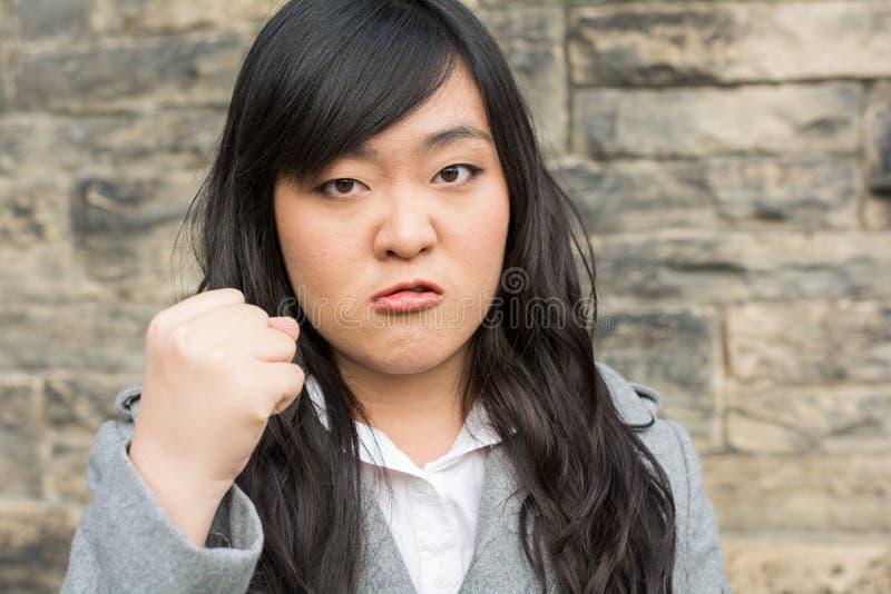 Mujer enojada por una pared de piedra fotos de archivo
