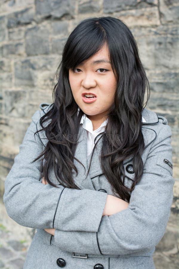 Mujer enojada por una pared de piedra fotografía de archivo